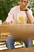 Young man waiting for someone in beer garden, Munich, Bavaria