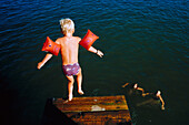 Young boy with waterwings, armbands, jumping into a lake, Learning, Childhood