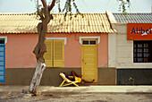 Teenager asleep in a deck chair, Street in Santa Maria, Santa Maria, Sal, Cape Verde Islands, Africa