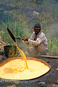 Man at huge cauldron filled with liquor of sugar cane, Paul, Santo Antao, Cape Verde, Africa