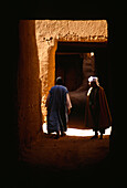 Two people standing in a passage way at the town Hara, Tinerhir, Marocco