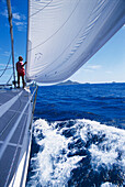 Man standing on the bow of a sailing boat at full speed, Petit Martinique, St. Vincent, Grenadinen, Caribbean, America