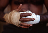 Boxer Little Lizard putting on bandages, getting ready for fight, Fred Brophy's Boxing Troupe, Australia