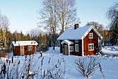 Wooden houses in snow covered scenery, Vastergotland, Sweden