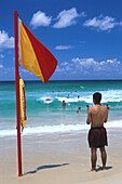 Man standing next to a flag on the beach watching the people in the water, Bondi Beach, Sydney, New South Wales, Australia