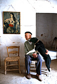 An old man and a dog in the farmworker's room of a finca, Son Brui, Majorca, Spain