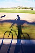 Shadow of a cyclist, country road near Sineu, Majorca, Spain