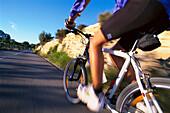 Man riding bicycle, siedeview, road near Sineu, Majorca, Spain