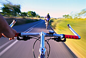Men riding bicycle, view from bicycle behind, road near Sineu, Majorca, Spain