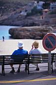 Senior couple sitting on bench, Cala Molins, Cala se Sant Vicenc, Majorca, Spain