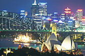 Opera House, Habour Bridge and Luna Park in front of illuminated high rise buildings, Sydney, New South Wales, Australia