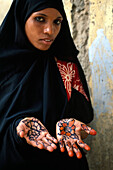 Portrait of a muslim woman with painted hands, Zanzibar, Tanzania, Africa