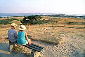 Couple sitting on a bench looking over Lake Hiddensee, Mecklenburg-Western Pomerania, Germany
