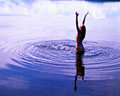 Woman standing in a lake, arms raised high, Sweden