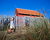 Little girl walking along fence and small house, Bornholm, Baltic Sea, Denmark
