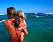 Woman standing in water, holding daughter on arms, Dueodde, Bornholm, Baltic Sea, Denmark