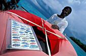 African man with life belt and information board on a boat, Chumbe Island, Zanzibar, Tanzania, Africa