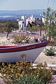 Fishing boat in front of clothesline in the sunlight, Ilha da Culatra, Parque Natural da Ria Formosa, Algarve, Portugal, Europe