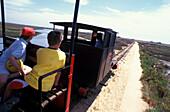 Tourists on a small train driving through the Parque Natural da Ria Formosa, Tavira, Algarve, Portugal, Europe