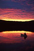 Man in boat on lake in sunset, Vaestergoetland, Sweden