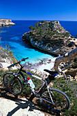 Mountainbike vor einer Bucht mit Strand unter blauem Himmel, Cala S´Amonia, Mallorca, Spanien, Europa
