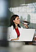 Businesswoman using a laptop, drinking a bottle of water, Vienna, Austria