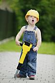 Boy 3-4 years, wearing hard hat holiding toy jackhammer, Styria, Austria