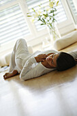 Girl relaxing at home, Girl relaxing at home, Young women sleeping on wooden floor, Home Lifestyle People Wellness