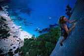 Female free climber scaling rock face, Cala Goloritze, Sardinia, Italy