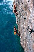 Couple freeclimbing up a rock face, Finale Ligure, Liguria, Italy
