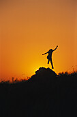 Silhouette of a woman jumping into the air, Sunset, vitality, South Afrika