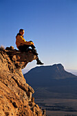 Mid adult woman sitting on a rock while looking at view, Harrismith, South Africa