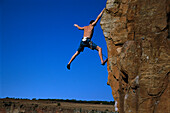 Climber stretches out arms and legs, Waterval Boven, South Africa