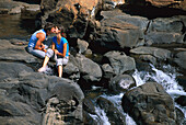 Couple kissing on rocks by a stream, Mpumalanga, South Africa