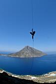Climber scaling up a rope, Kalymnos, Greece