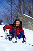 Woman sitting in the snow and laughing after fall, Muehlviertel, Upper Austria