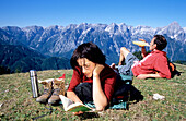 Couple of hikers relaxing on mountain pasture, Hutterer Hoess, Kalkalpen National Park, Muehlviertel, Upper Austria, Austria