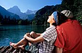 Couple of hikers relaxing at mountain lake, Hutterer Hoess, Kalkalpen, Muehlviertel, Upper Austria, Austria