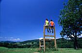 Couple sitting on a giant chair, Bankerlsteig, Muehlviertel, Upper Austria, Austria