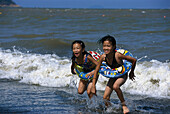 Two girls on the beach having fun in the sea, Hac-Sa Beach, Coloane Island, Macao, China