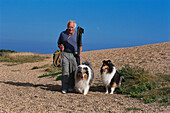 Fisherman and dogs, Chesil Beach, Dorset, England
