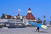 Surfer walking along the beach with surfboard, Hotel del Coronado, California USA