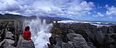 Woman sits atop Pancake Rocks in Paparoa National Park, Punakaiki, West Coast, South Island, New Zealand