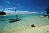 Frau am Strand mit Boot, Ile aux Cerfs, Mauritius