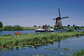 Windmill at a riverbank, Kinderdijk, Netherlands, Europe
