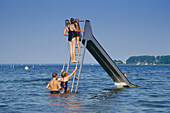 Bathing children on water slide, Mueritz Lake, Mecklenburgian Lake District, Mecklenburg-Western Pomerania, Germany