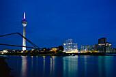 Illuminated buildings of the media harbour at night with Rheinturm and Neuer Zollhof, Duesseldorf, North Rhine Westfalia, Germany