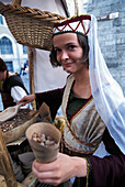 Young woman selling almonds in front of Olde Hansa restaurant, Tallinn, Estonia, Europe