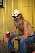 Man is sitting in front of the house drinking beer, Key West, Florida Keys, Florida, USA