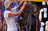 Female tourist choosing a necklace at the Hippie market, Sant Miquel, Ibiza, Spain